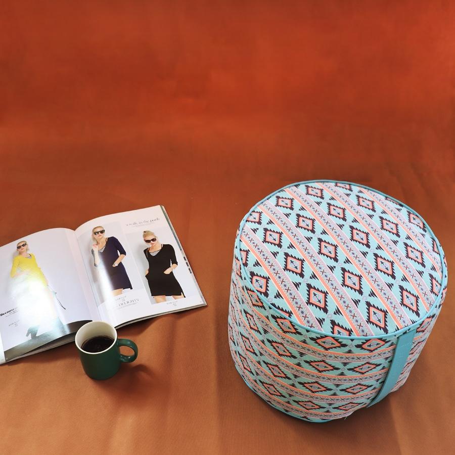 Pouf tondo con stampa geometrica azzurra nera e rosa, più rivista e tazza