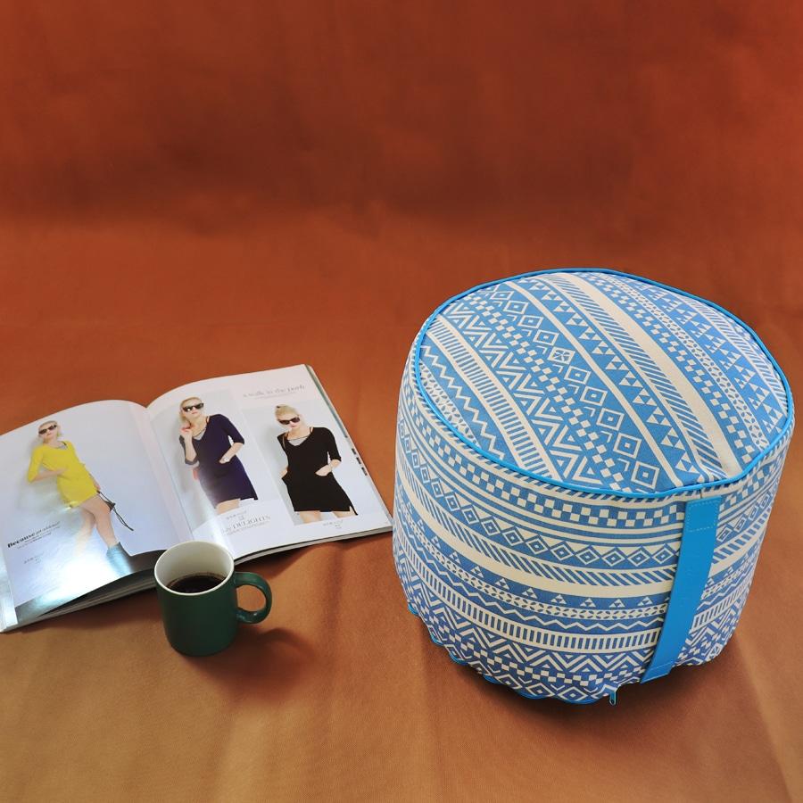 Pouf tondo con fantasia geometrica blu, rivista e tazza