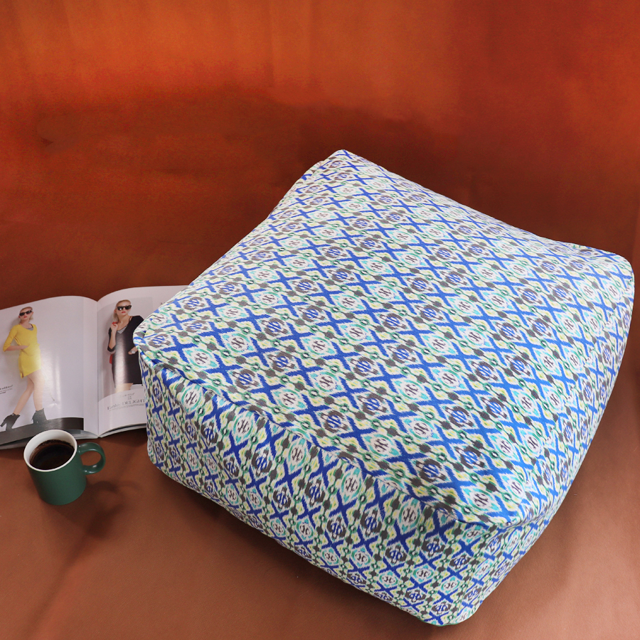 Pouf squadrato con stampa geometrica blu, rivista e tazza