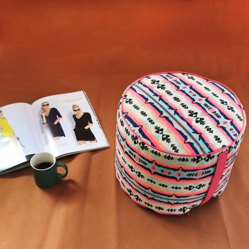 Pouf tondo con stampa geometrica fucsia, rivista e tazza