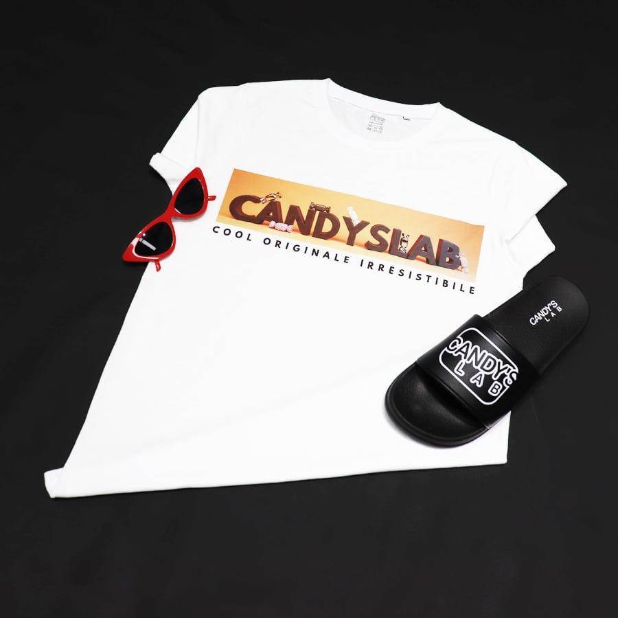 Maglietta bianca con scritta candyslab più ciabatta nera e occhiali rossi
